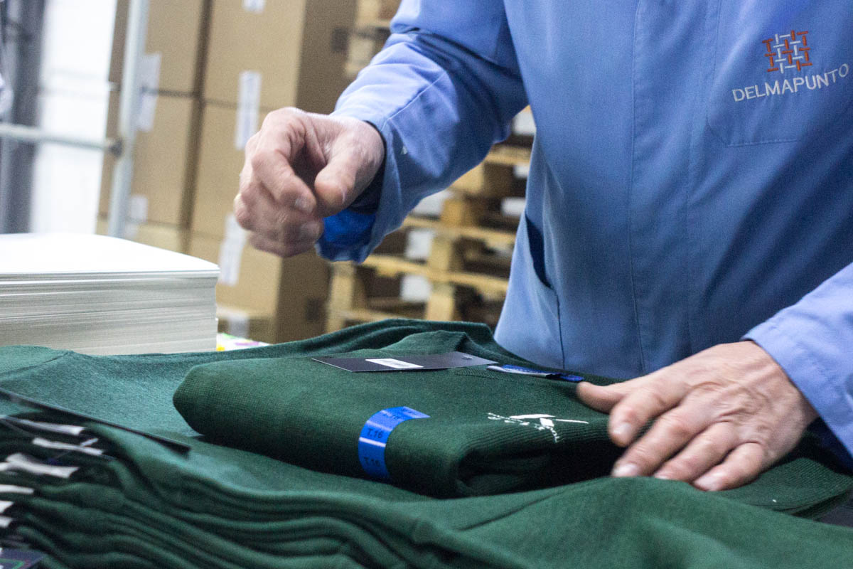 persona empaquetando un uniforme escolar en delmapunto confecciones